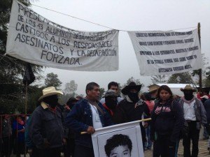 Families of the 43 disappeared student-teachers of Ayotzinapa standing with photos in front of the Zapatista caracol of Oventic in the highlands of Chiapas, Mexico.
