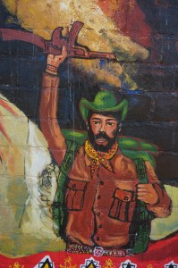"This painting of Sub-commander was painted under the direction of Mitzi and Gustavo in 2014; the health clinic in La Realidad will be named ""The Autonomous Zapatista Health Clinic of Subcommander Pedro. We believe this image will be reborn anew during the Easter 2015 painting."