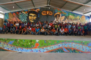 Zapatista education promoters, delegates and autonomous authorities gathered in front of a newly painted mural.