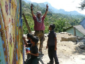 Artist in resistance, Gustepe, painting a mural in Zapatista territory with the kids who always are included in these mural projects.
