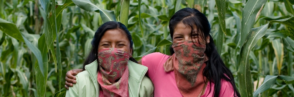 Two young Zapatista students smiling through their signature red masks while standing in front of their school garden in Chiapas, Mexico.